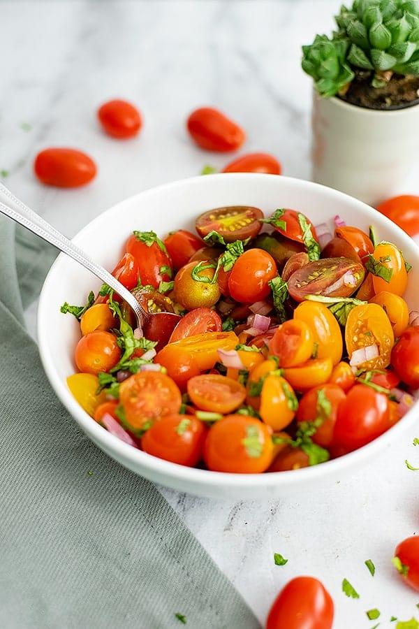 Bowl of tomato basil salad over a grey napkin