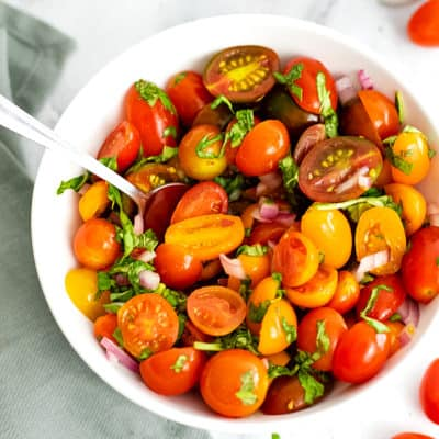 Overhead shot of large white bowl filled with tomato basil salad.