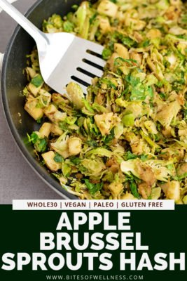 Large skillet filled with apple brussel sprouts hash with a silver spatula digging into the hash with pinterest text on the bottom