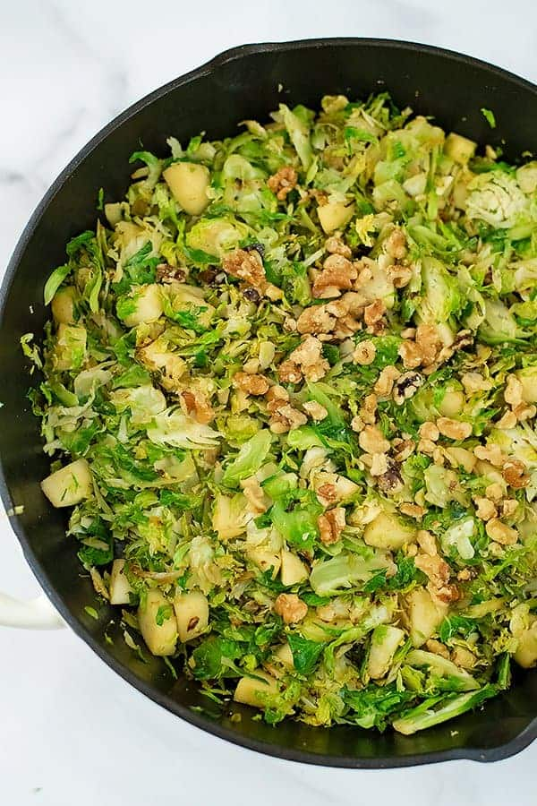Adding the chopped nuts to the apple brussel sprouts hash in skillet.