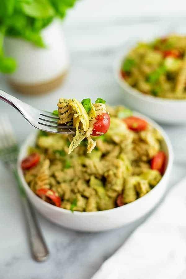 Fork holding a bite of artichoke pesto pasta