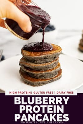 stack of 4 pancakes being with blueberry syrup poured over top