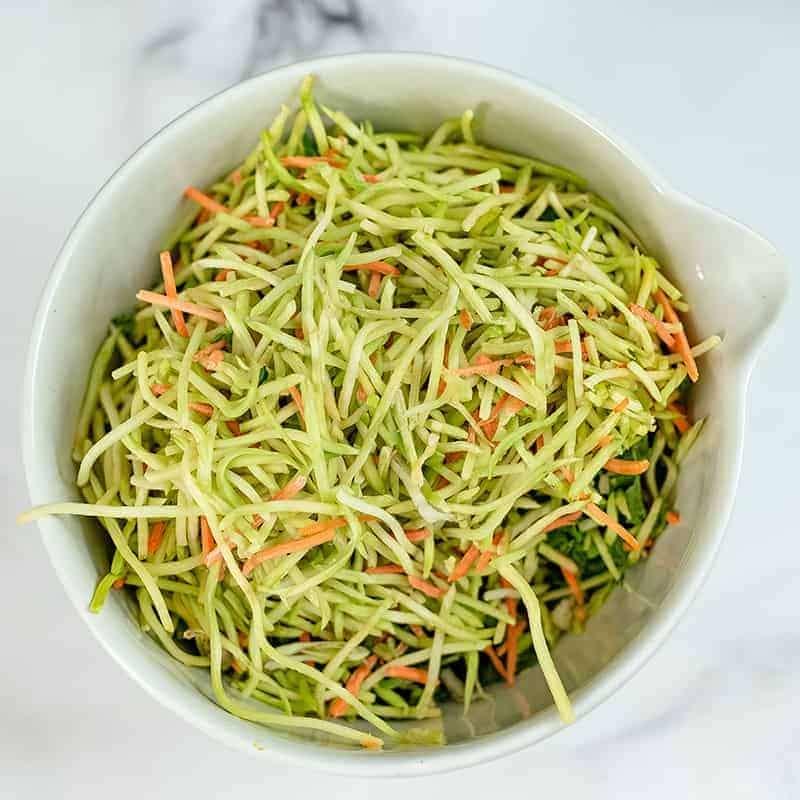 Broccoli slaw in a large white bowl