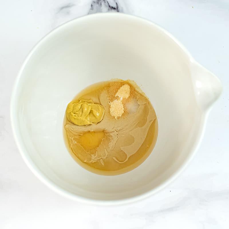 Large white bowl filled with lemon tahini dressing ingredients