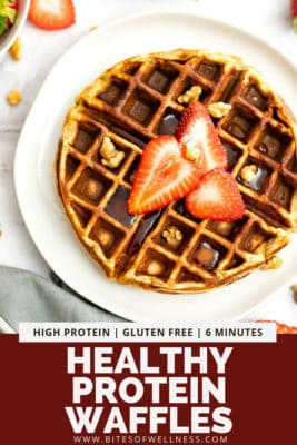 Gluten free protein waffles with syrup and strawberry slices on a white plate.