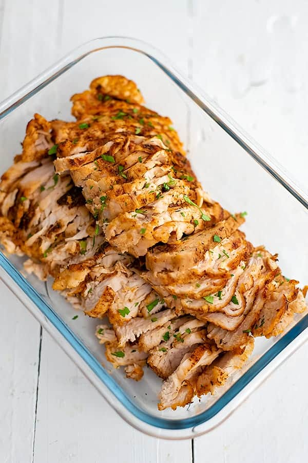 Thinly sliced baked chicken breast in a rectangular glass dish.