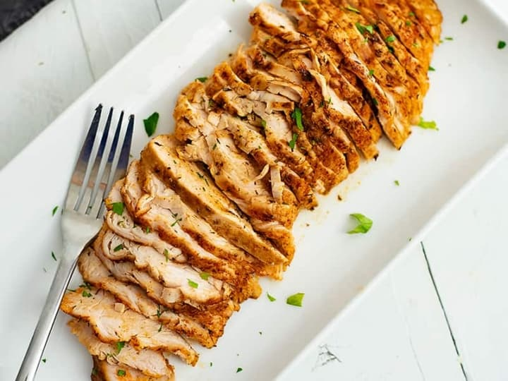 Thinly sliced oven baked chicken breast on white plate with fork