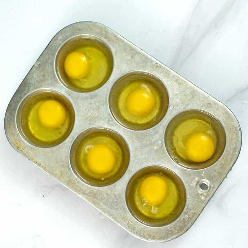 Raw eggs cracked into the muffin tin