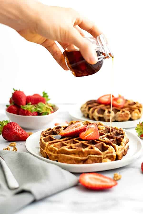 Syrup being poured over protein waffles