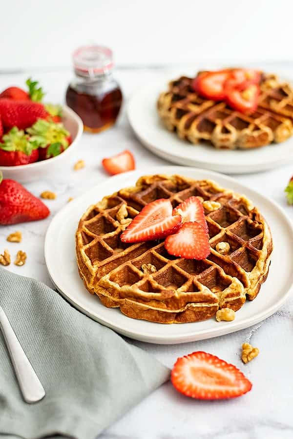 Two protein waffles with strawberries on top with syrup in the background