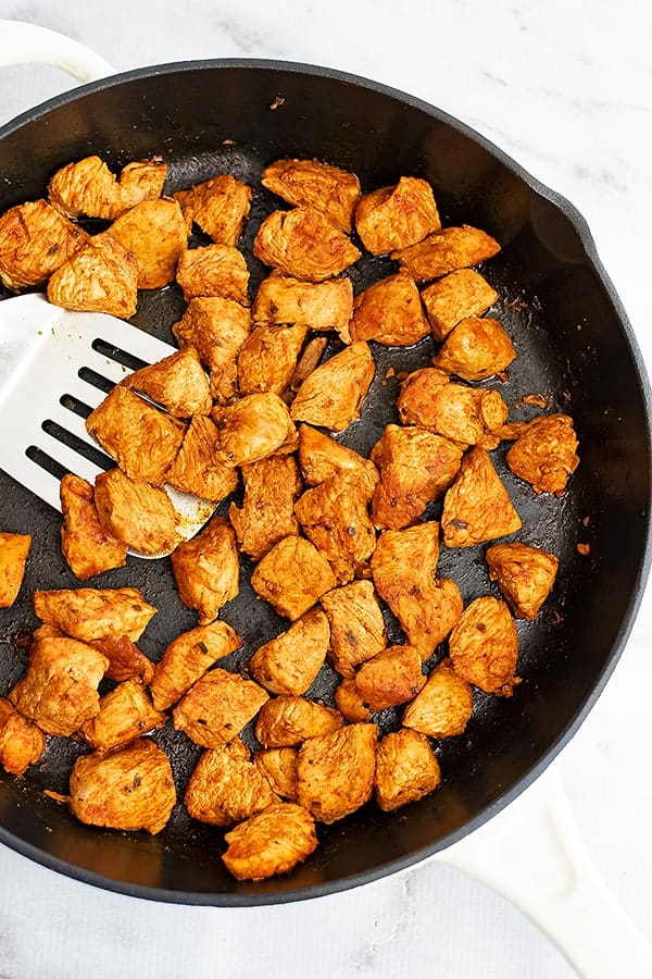 Cast iron skillet filled with taco chicken meat