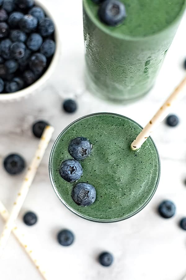 Looking down on a spinach blueberry smoothie with a straw in the glass