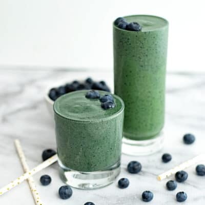 Two glasses of spinach blueberry smoothie with blueberries surrounding them
