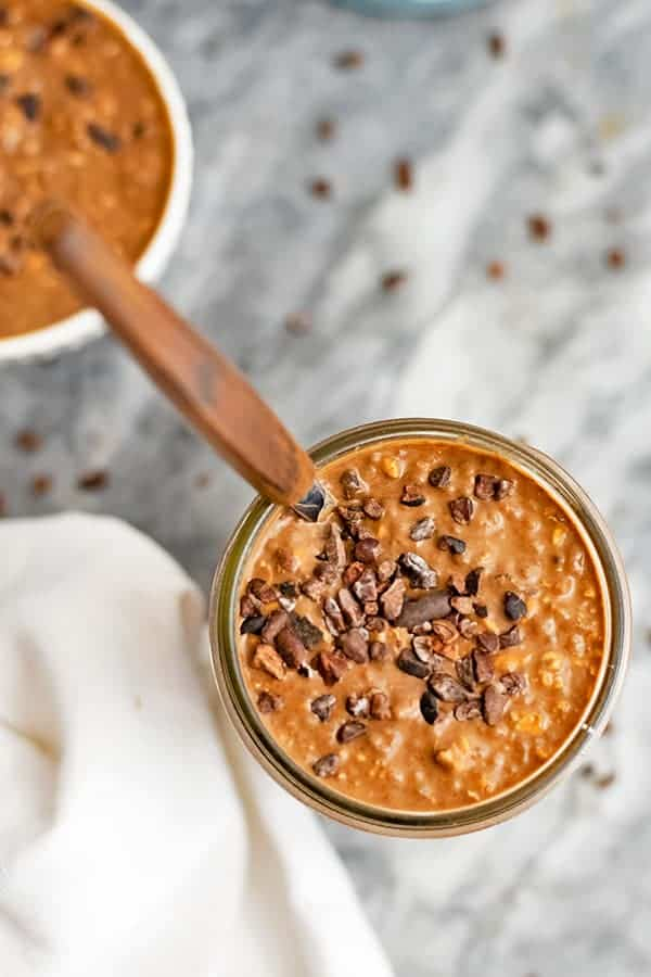 Looking down on a full jar of overnight oats with a spoon.