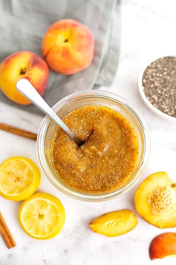 Jar of peach chia jam with a spoon in the jar