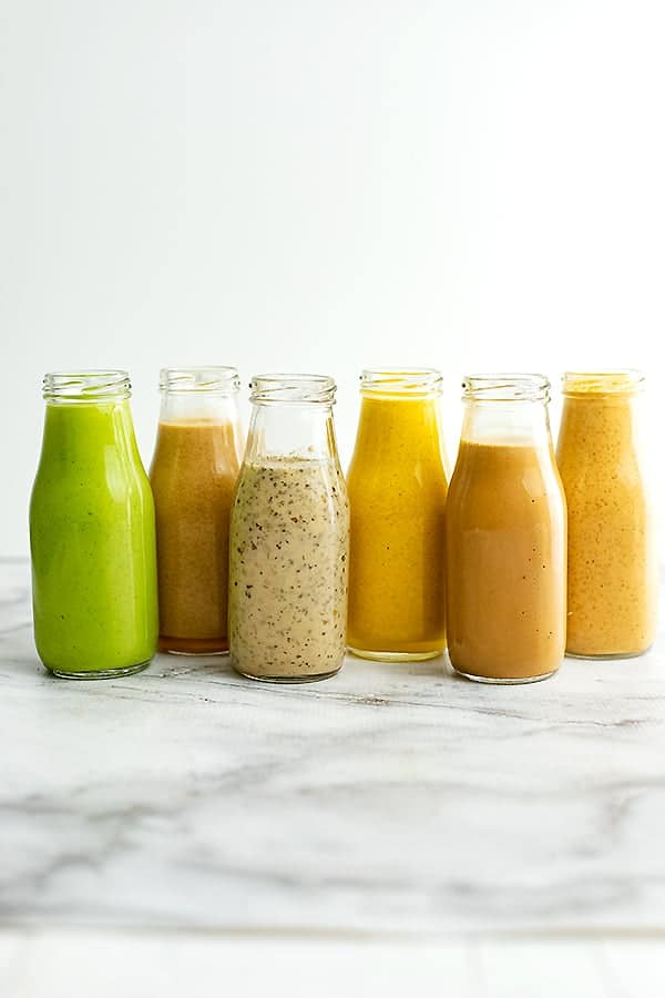 Glass bottles lined up with 6 Healthy Salad Dressing Recipes
