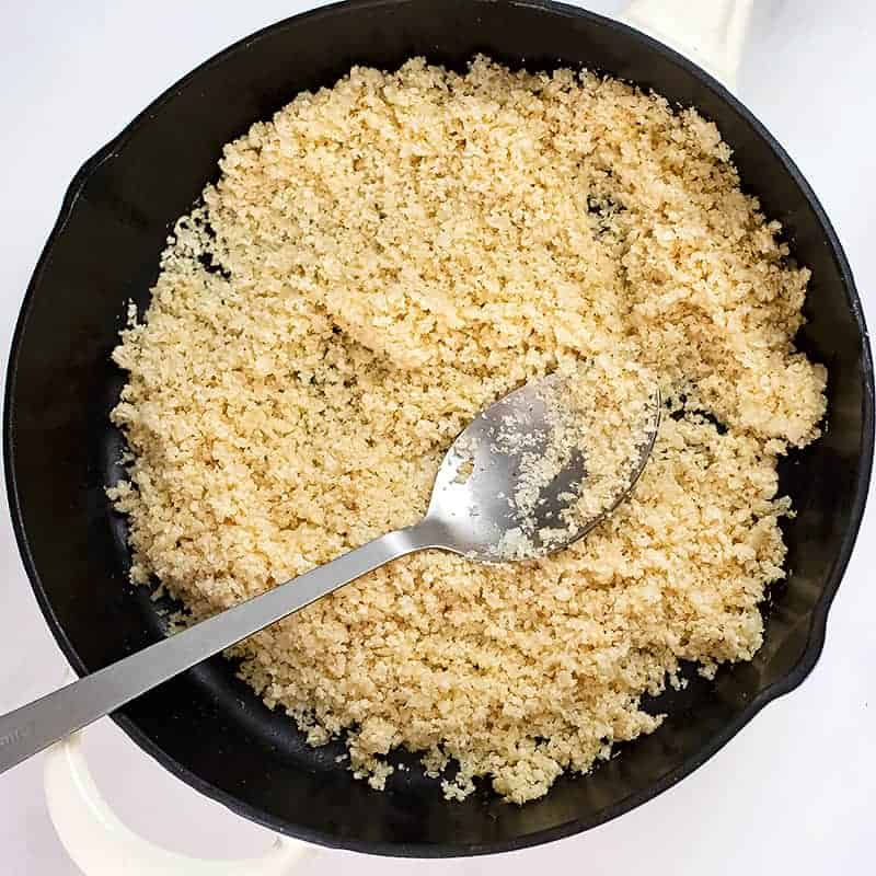 Cooked cauliflower rice in a cast iron skillet