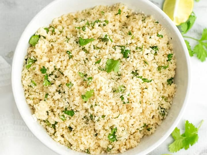 Large white bowl filled with cilantro lime cauliflower rice with limes around the bowl.