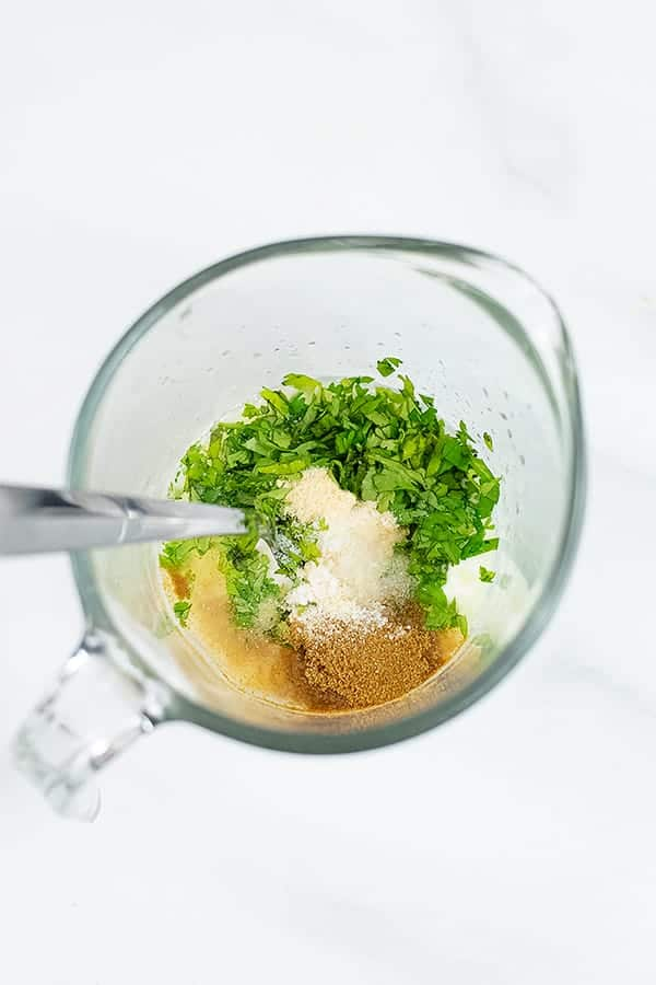 Glass measuring cup filled with ingredients for cilantro lime yogurt sauce