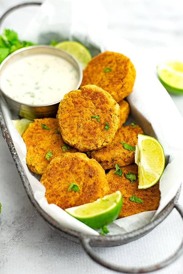 Curry Salmon Cakes piled high in a serving dish with cilantro lime yogurt sauce.