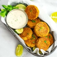 Curry Salmon Cakes in grey basket with cilantro lime yogurt sauce