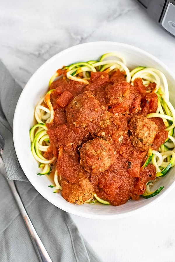 Large bowl filled with zucchini noodles topped with Whole30 turkey meatballs.