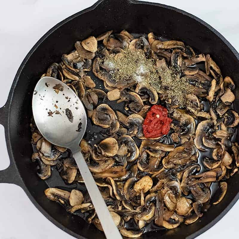 Cooked mushrooms in a skillet with spices, tomato paste on top.