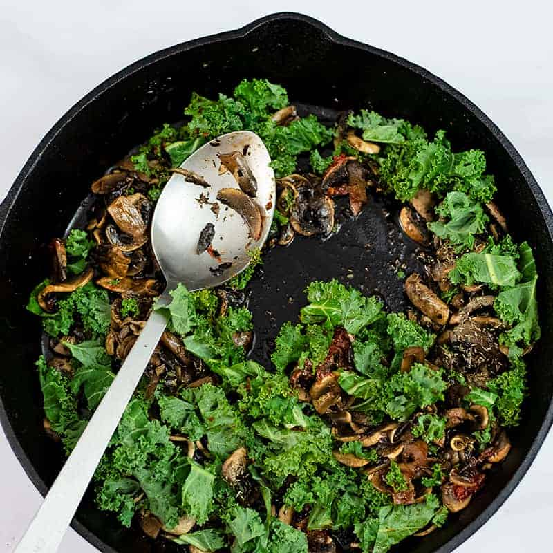Fresh arugula wilting on cooked mushrooms in a skillet.