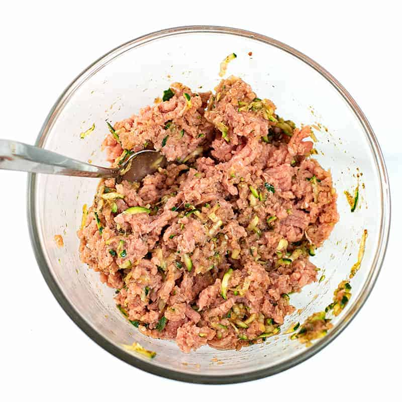 Glass bowl filled with ground turkey mixed with spices.