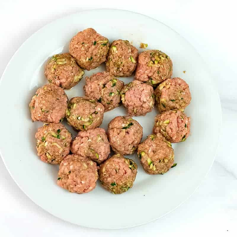 Whole30 Turkey meatballs formed before cooking on a white plate
