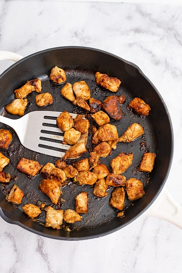 Large cast iron skillet filled with Asian Chicken and a silver spatula.
