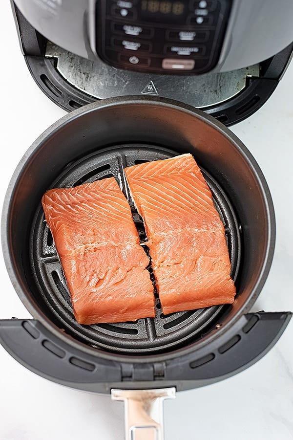 Raw salmon in an air fryer basket.