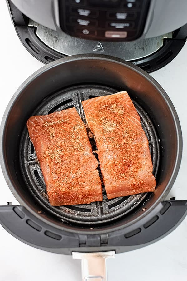 Salmon in the air fryer with seasoning sprinkled on raw salmon.