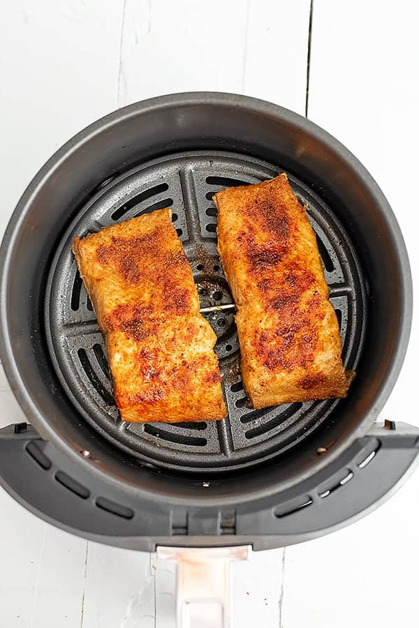 Salmon in air fryer basket after cooking.
