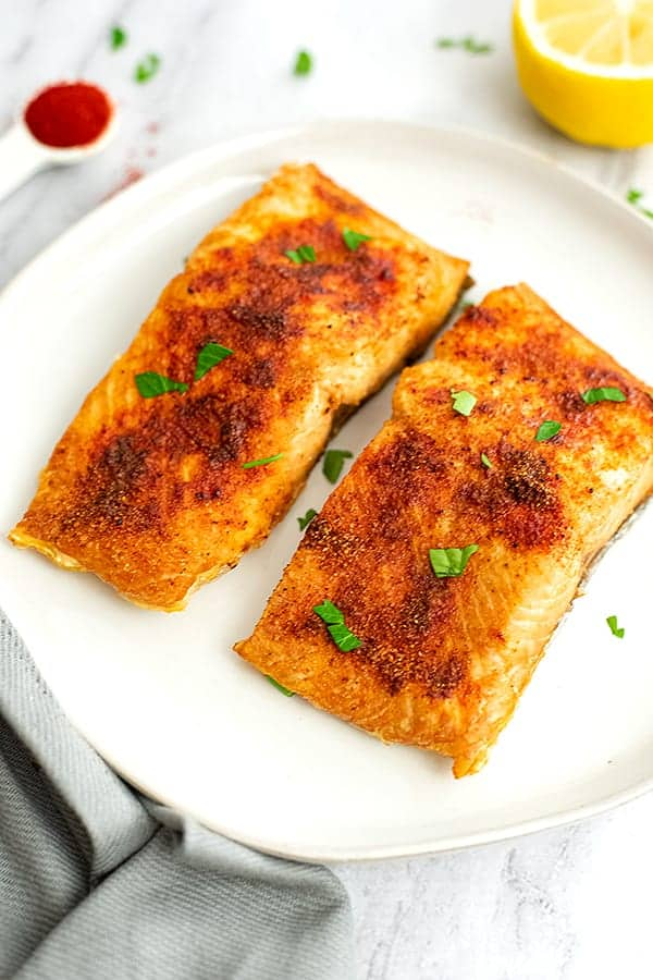 Two pieces of air fryer salmon on a white plate.