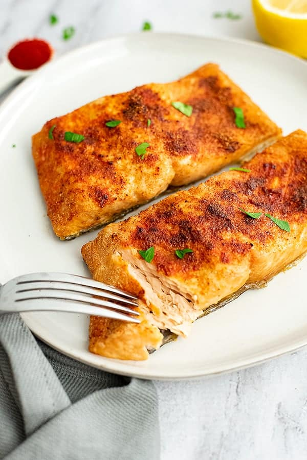 Fork flaking air fryer salmon on a white plate.