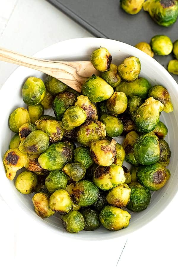 Large bowl filled with roasted brussel sprouts and a wooden spoon.