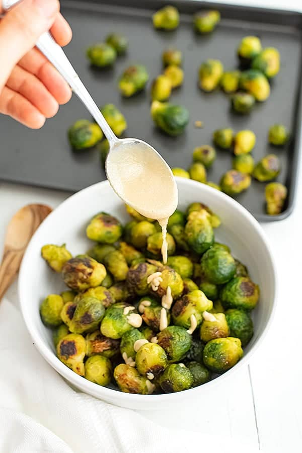 Spoon drizzling tahini over roasted brussel sprouts.