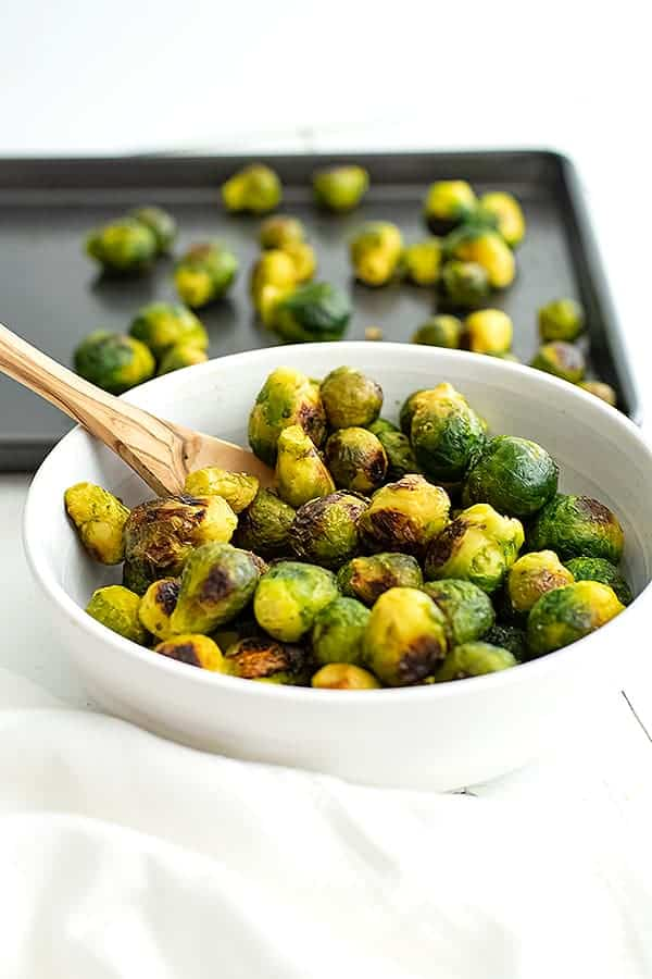 White bowl filled with roasted frozen brussel sprouts and wooden spoon.