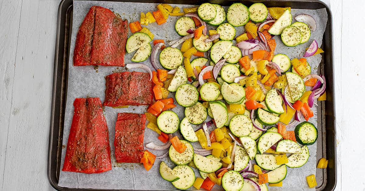 Large sheet pan filled with raw Greek salmon and vegetables.