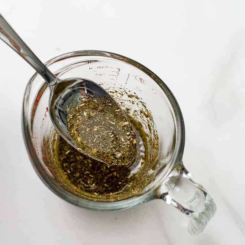 Glass measuring cup filled with greek marinade with a spoon in the cup.