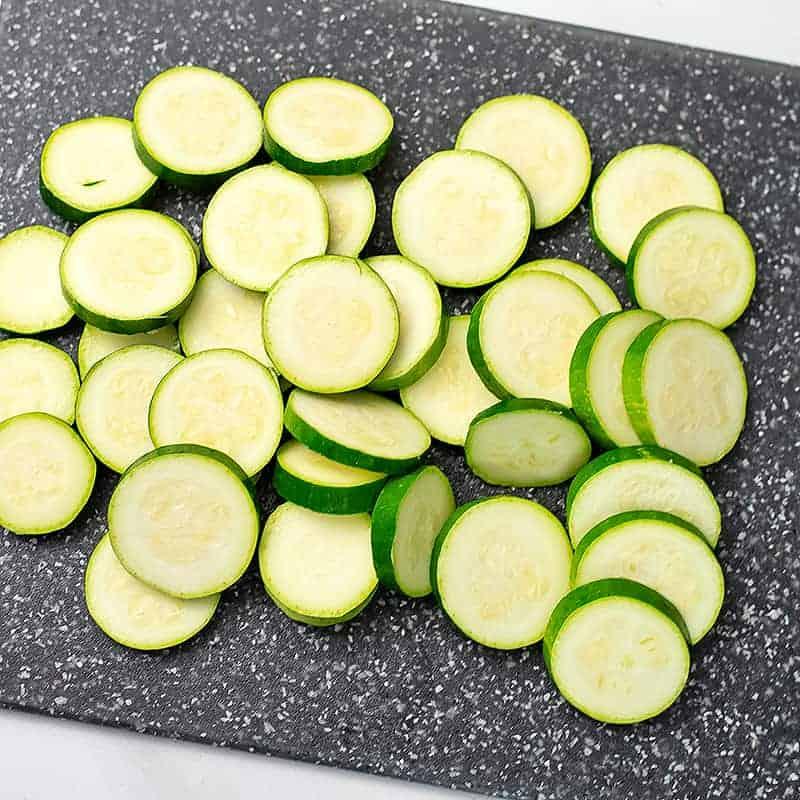 Zucchini cut into coins on a cutting board.