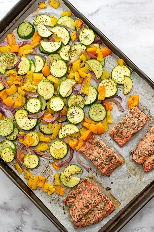 Large sheet pan filled with cooked Greek salmon and vegetables.