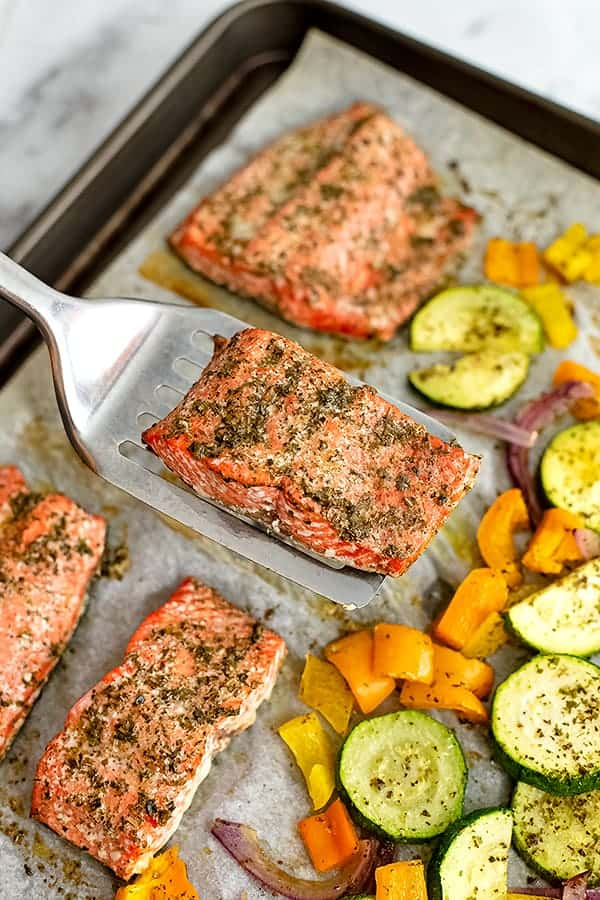 Spatula holding a piece of greek salmon over the sheet pan.
