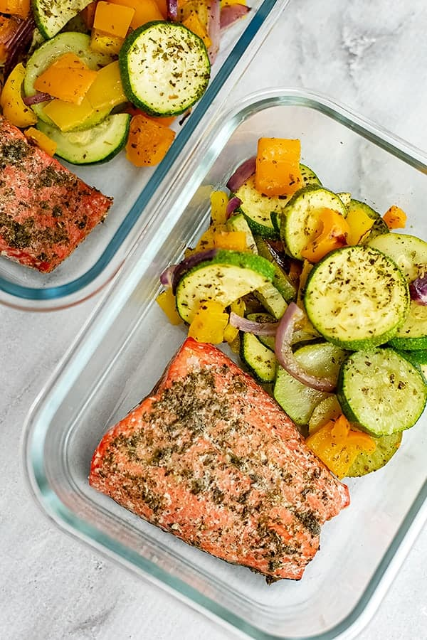 Glass storage container filled with Greek salmon and vegetables.