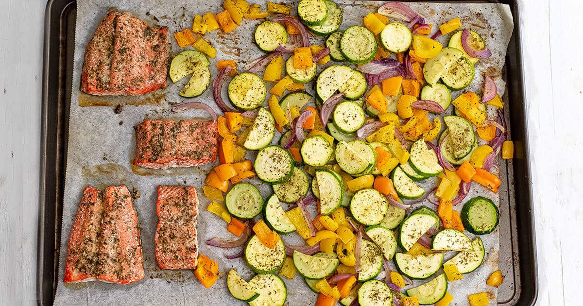 Baking sheet filled with cooked greek salmon and vegetables.