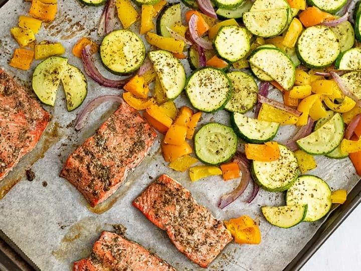 Greek salmon and veggies on a baking sheet after baking.