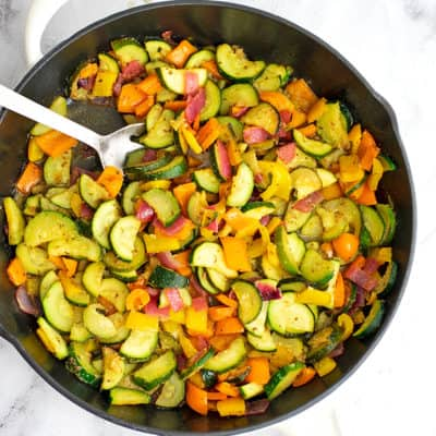 Greek vegetables in a cast iron skillet with silver serving spoon.