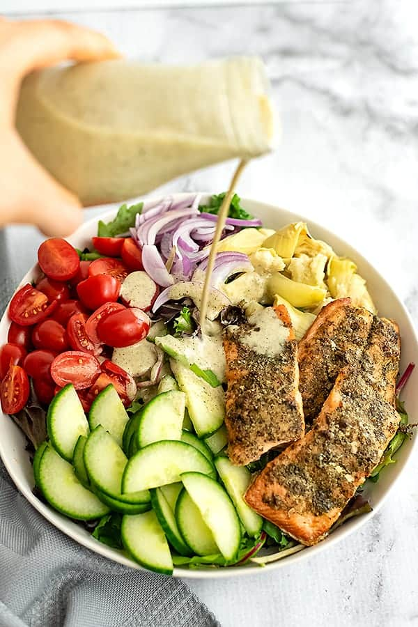 Dressing being poured over a bowl of italian salmon salad.