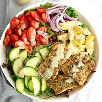 Large bowl of Italian Salmon Salad with dressing poured on top.